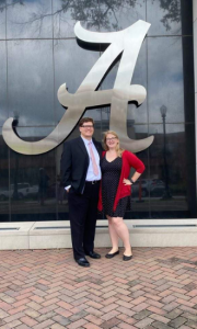 Brandon and his wife in front of a large, silver script A at graduation
