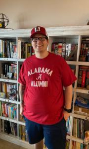 "Brandon standing in front of a bookshelf wearing an ""Alabama alumni"" tshirt and an Alabama hat"