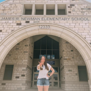 Becca holding up four fingers in front of her school, Newman Elementary
