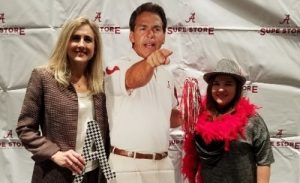 Candida at the Bama By Distance graduation reception with Professor Pentecost in front of a cardboard cutout of Nick Saban