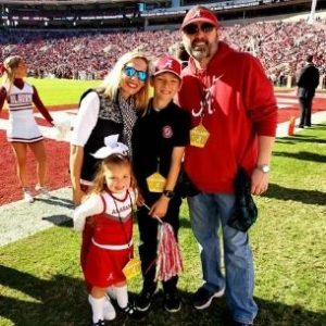Jessica and her family on the field at Bryant-Denny Stadium during a game