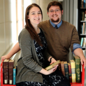 Noella and her husband sitting in a library