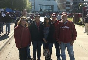 Rachel and her family in Alabama clothing outside of Bryant-Denny Stadium