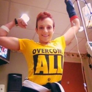 "Kristen in the hospital flexing her bicep with an ""Overcome All"" shirt on"
