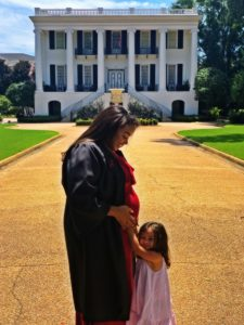 Franky with her daughter in front of the UA president's mansion on the day she graduated with her bachelor's. In the photo, she is looking down at her pregnant belly through her graduation robe opening, and her daughter is hugging her belly.