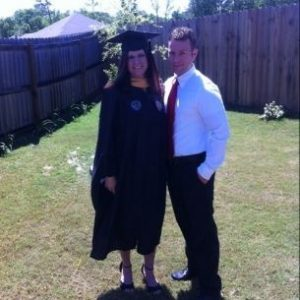Jessica with her husband in her graduation robe when she graduated with her MSW
