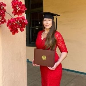 Kristi Collins in her graduation cap holding her diploma
