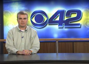 Michael at the anchor desk in front of the CBS 42 logo