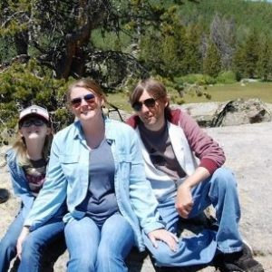 Kimberly with her husband and daughter with a nature scene behind them